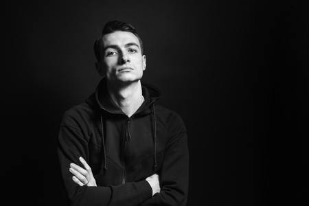 Black and white studio portrait of a young man in a black sweatshirt, arms crossed, seriously looking at the camera, against plain studio background