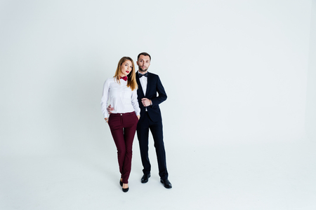 Close up studio portrait of stylish young couple, pretty woman and handsome man looking to the camera, against plain studio background.