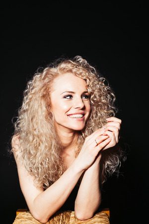 Close up studio portrait of a pretty curly blonde woman, laughing and looking to the side, against plain studio background