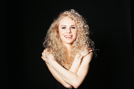 Close up studio portrait of a pretty curly blonde woman, smiling and looking at the camera, hands on the shoulders, against plain studio background