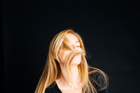 Close up portrait of a woman enjoying a silly moment while posing against a black background in a studio