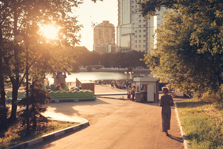 Woman walking along the road to the river bank on the sunset in a landscape urban park