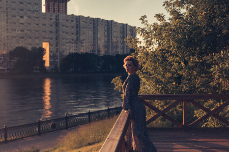 Woman standing on a wooden stairs in an urban landscape park, watching the Sunset