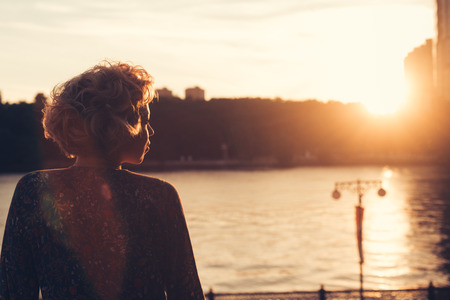 Woman watching the sunset in a park on the river bank