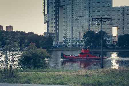 Red tug boat passing the city park, high-rise building on the background Stock Photo