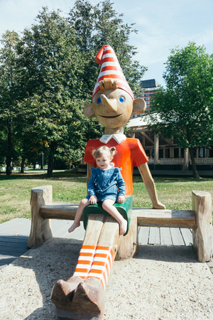 Portrait of a 3 years old girl sitting on a wooden statue of Pinocchio in a city park on a warm sunny day Stockfoto