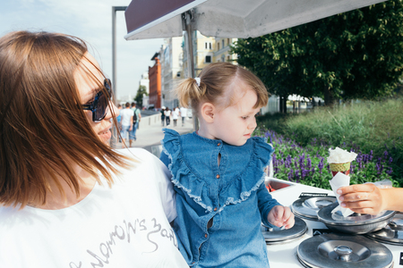 Portrait of a young mother and her 3 years old daughter buying ice cream in a city park on a warm sunny day