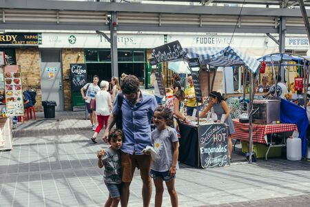 London, UK - July 23, 2018: Young family - dad with two kids walking inside the Greenwich Market, one of the oldest markets in London, UK
