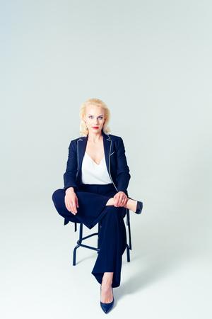 Studioporträt der schönen blonden Frau in einem schwarzen Kleid gegen weißen einfachen Hintergrund plain