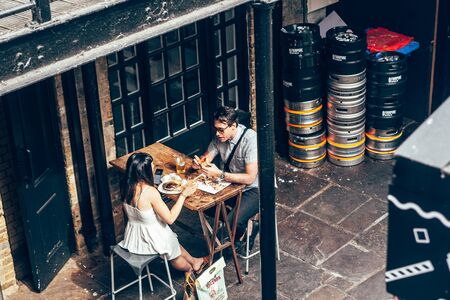 London/UK - July 17, 2019: couple having lunch at the table at Camden Market sitting area. Camden Market is the fourth-most popular visitor attraction in London. Selective focus
