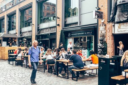 London/UK - July 17, 2019: people eating their food at Camden Market sitting area. Camden Market is the fourth-most popular visitor attraction in London. Selective focus