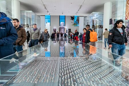 London/UK- Nov 28, 2019: an installation by Pharmacopoeia in Room 24 in the British Museum, called Cradle to Grave, looks at an approach to health and wellbeing; people in motion blur, selective focus Редакционное