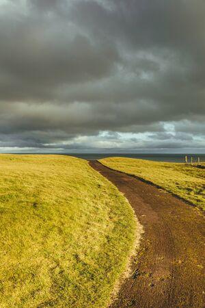 Sunlight over green fields and coastal path near Brora village on the North sea coast of Scotland, UK Stock Photo