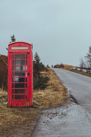 Traditional red telephone box on a side of a road in the Scottish Highlands;