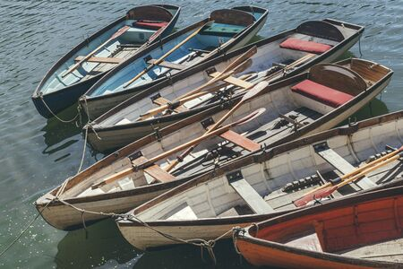 Wooden rowboats with oars inside, moored at the Thames riverside