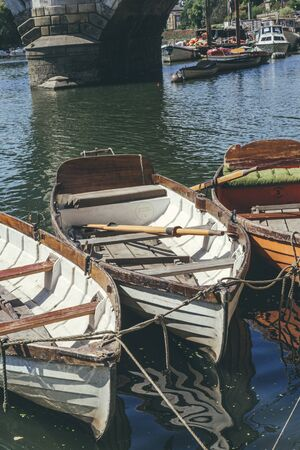 Wooden rowboats with oars inside, moored at the Thames riverside near Richmond Bridge Stok Fotoğraf