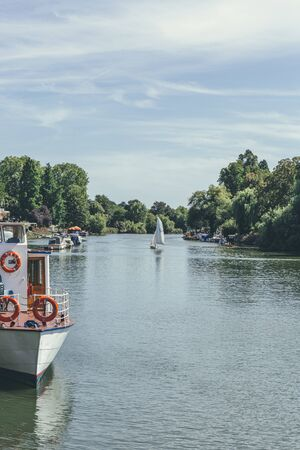 A sailboat with white sails maneuvers on the River Thames near Richmond riverside on a sunny summer day. A sailboat or sailing boat is a boat propelled partly or entirely by sails
