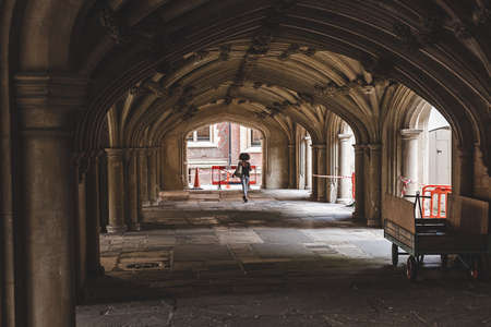 Woman walking under the 17th century vaulted undercroft below the Lincoln's Inn chapel which has acted (sometimes simultaneously) as a crypt, meeting place and place of recreation.