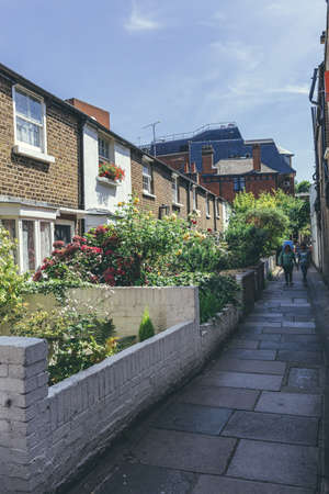 London/UK-1/08/18: A couple walking in a narrow passage between the terraced houses in London on a sunny summer day. Happy relationship concept; selective focus