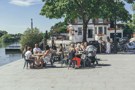 London/UK-1/08/18:people relaxing in the sitting area of The White Cross, Richmond's riverside pub, on a hot sunny day. Pubs are a social drinking establishment and a prominent part of British culture