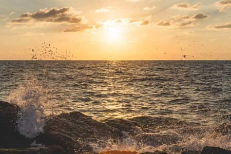 Waves crashing off the rocks with millions of splash droplets around during the scenic sunset over the Mediterranian Sea as seen from a waterfront in Tel Aviv, Israel