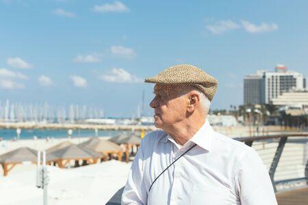 Close up portrait of an older man in a flat cap on a beach in Tel Aviv, Israel