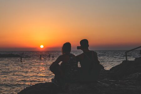 Silhouette of an unidentified couple taking a selfie while seeing off the sunset over the Mediterranean Sea on the seacoast in Tel Aviv, Israel on a warm evening Stock Photo