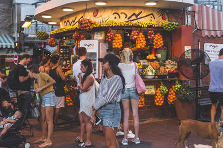 Tel Aviv/Israel-12/10/18: people standing in a line to the popular local fruit bar, Tamara, located on the crossroad of Dizengoff and Ben Gurion Streets in Tel Aviv