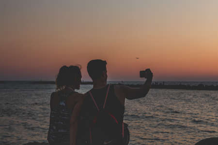 Tel Aviv/Israel-13/10/18: Silhouette of an unidentified couple taking a selfie while seeing off the sunset over the Mediterranean Sea on the seacoast in Tel Aviv, Israel on a warm evening
