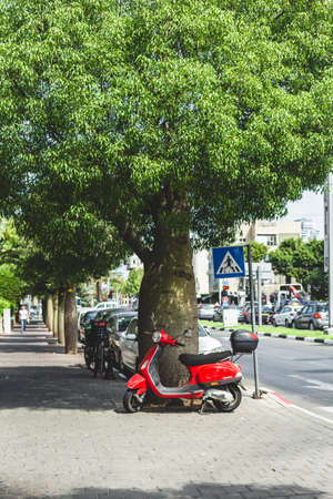 Tel Aviv/Israel-9/10/18: red Vespa scooter parked on a sidewalk under the tree in Tel Aviv. Vespa is one of the most famous Italian brands of scooters in the world known for its design Sajtókép