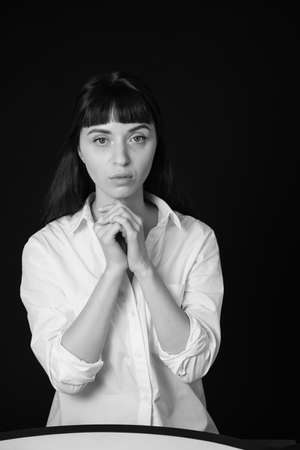 Studio portrait of a pretty brunette woman in a white shirt, against a plain black background, holding both hands together, near face
