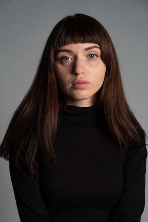 Studio portrait of a pretty brunette woman, wearing folded black polo-neck sweater, looking at camera, against a plain grey background