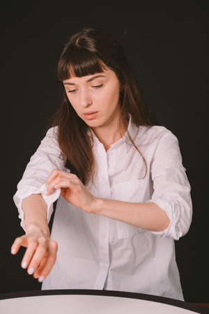 Studio portrait of a pretty brunette woman in a white shirt, rolling up the sleeve, against a plain black background
