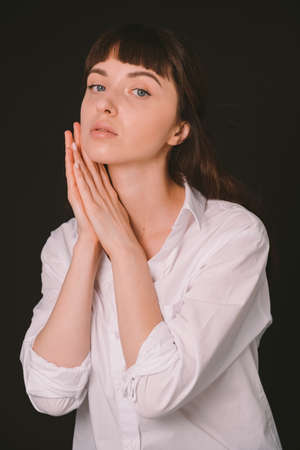 Studio portrait of a pretty brunette woman in a white shirt, against a plain black background, holding both hands together, near face, looking at the camera