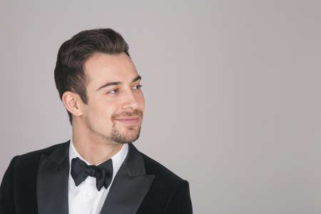 Studio portrait of a young caucasian man in a tuxedo, looking to the side, against plain studio background