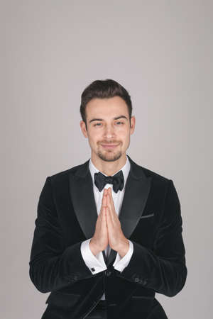 Studio portrait of a young caucasian man in a tuxedo, hands together, looking at the camera, against plain studio background