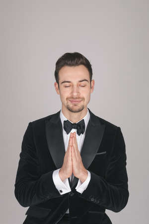 Studio portrait of a young caucasian man in a tuxedo, eyes closed, hands together, against plain studio background