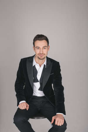 Studio portrait of a young caucasian man in a tuxedo, collar unbuttoned, bow tie untied, looking at the camera, against plain studio background