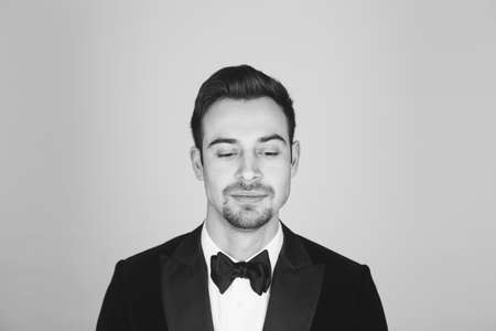 Studio portrait of a young caucasian man in a tuxedo, upset, looking down, against plain studio background
