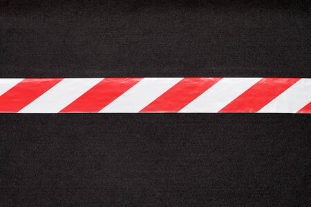 tape line: Red and white warning tape on the black carpet.