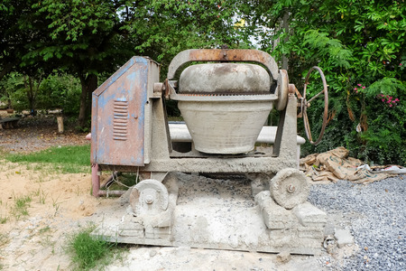 cement pile: Small cement mixer on a pile of rocks and sand. Stock Photo