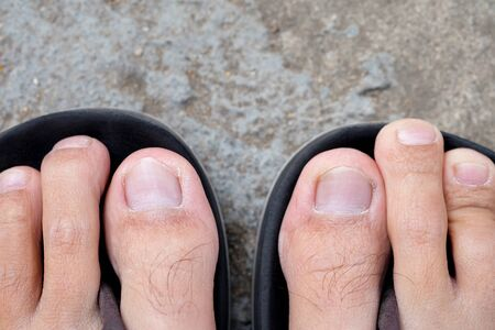 wearing sandals: Feet of men wearing black sandals on the cement floor. Stock Photo