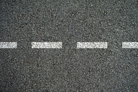 The lines on the asphalt road surface.