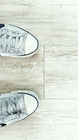 canvas: Old white shoes on a wooden floor. Stock Photo