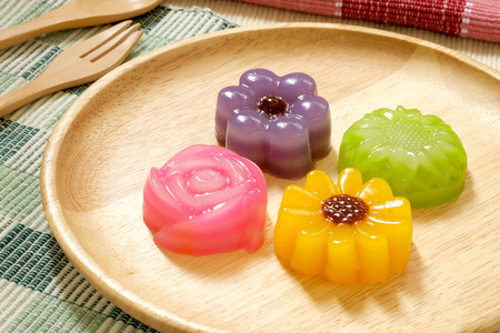 Layer Sweet Cake or Kanom Chan flowers on wooden plates, Thai dessert.