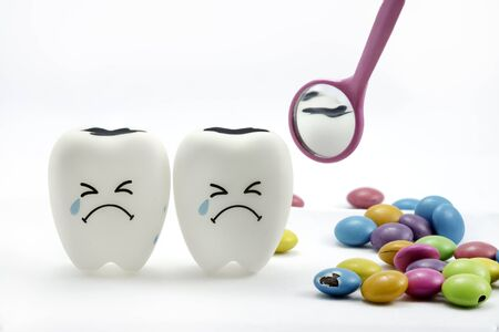 Tooth decay is crying with dental mirror and sugar coated chocolate on the side. On a white background Reklamní fotografie