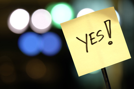 The concept of voting, signboard with the word Yes! on abstract light background