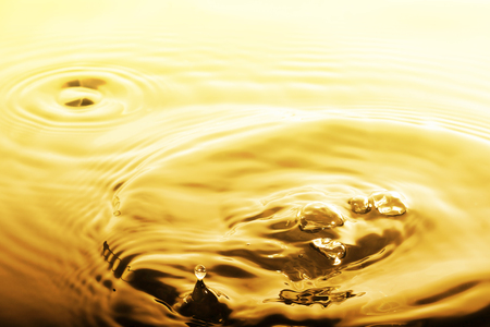 ripple: Liquid gold drop and ripple ,abstract background