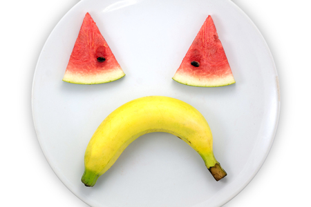 Watermelon slice and banana sad faces on white plate on white background , concept enjoy eating.