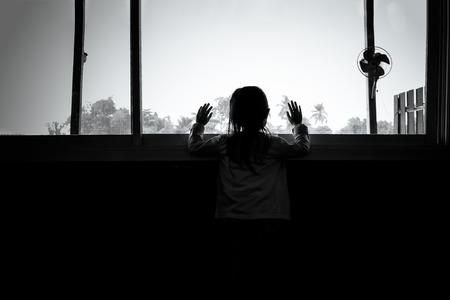 아시아 자식 소녀는 윈도우, 블랙 슬픈 기분, 그리고 화이트 톤을 찾고, 어둠 속에서 서있다.
